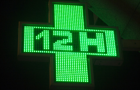12 hour: Pharmacy neon light chemists 12 hour open cross sign at night photo.