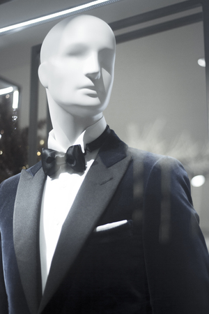 bow window: Shop dummy fashion mannequin in department store boutique window wearing evening suit dinner jacket and bow tie. Stock Photo