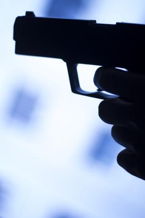 finger on trigger: Automatic 9mm pistol handgun weapon in blue photo.