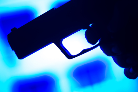 finger on trigger: Automatic 9mm pistol handgun weapon in blue photo.