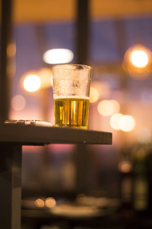 bar ware: Beer glass in restaurant bar nightclub in festive party at dusk with sunset background in Ibiza Spain. Stock Photo