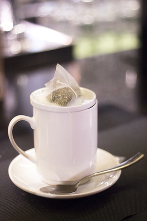 bar ware: Herbal tea infusion cup, spoon, saucer and teabag in cafe on restaurant bar. Stock Photo