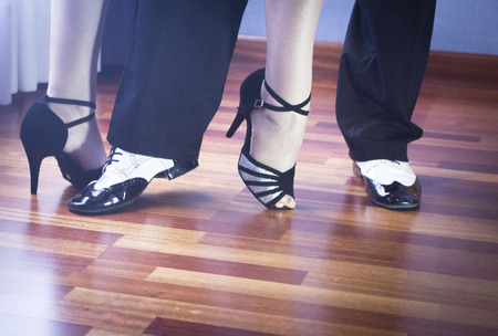salsa dance: Male and female ballroom, standard, sport dance, latin and salsa couple dancers feet and shoes in dance academy school rehearsal room dancing salsa.