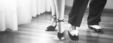 Male and female ballroom, standard, sport dance, latin and salsa couple dancers feet and shoes in dance academy school rehearsal room dancing salsa. Banco de Imagens - 54180911