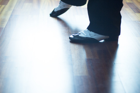 jive: Male ballroom, standard, sport dance, latin and salsa dancer feet and shoes in dance academy school rehearsal room dancing jazz fusion. Stock Photo