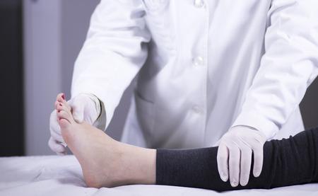 Traumatología y ortopedia cirujano ortopédico médico y el paciente consulta examen médico de los pies, los tobillos y dedos de los pies en la clínica hospitalaria.
