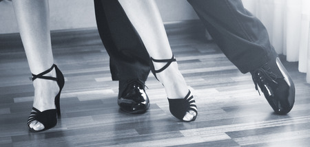 rehearsal: Male and female ballroom, standard, sport dance, latin and salsa couple dancers feet and shoes in dance academy school rehearsal room dancing salsa.