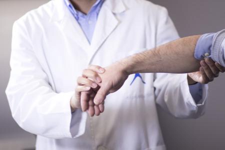Traumatología y ortopedia cirujano en el médico y el paciente consulta ortopédica examen médico para la mano, los dedos, el brazo y la muñeca en la clínica hospitalaria.