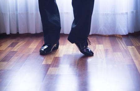 paso doble: Male ballroom, standard, sport dance, latin and salsa dancer feet and shoes in dance academy school rehearsal room dancing salsa.