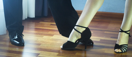 taniec: Male and female ballroom, standard, sport dance, latin and salsa couple dancers feet and shoes in dance academy school rehearsal room dancing salsa.