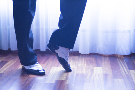 rehearsal: Male ballroom, standard, sport dance, latin and salsa dancer feet and shoes in dance academy school rehearsal room dancing salsa.