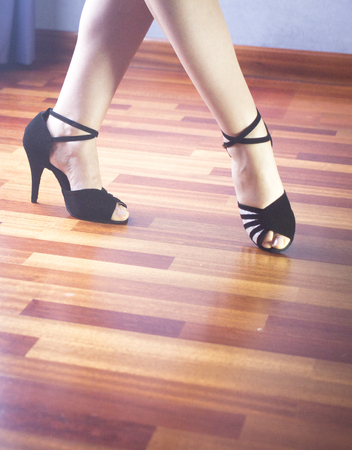 Female ballroom, standard, sport dance, latin and salsa dancer feet and shoes in dance academy school rehearsal room dancing salsa.
