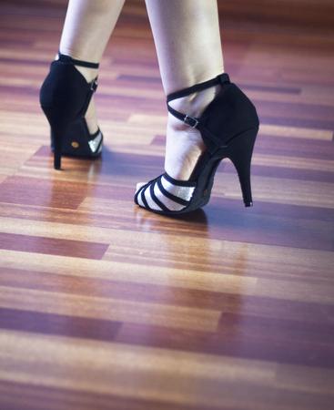 paso doble: Female ballroom, standard, sport dance, latin and salsa dancer feet and shoes in dance academy school rehearsal room dancing salsa.