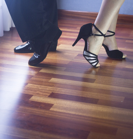 latino dance: Male and female ballroom, standard, sport dance, latin and salsa couple dancers feet and shoes in dance academy school rehearsal room dancing modern contemporary style.