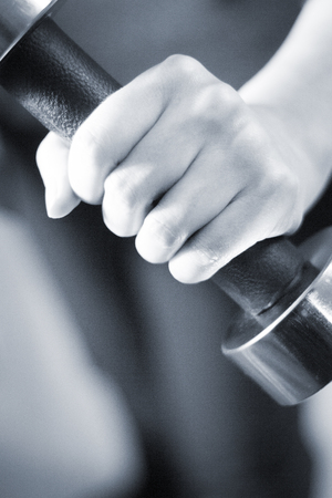 chromed: Male bodybuilder lifting chromed metal dumbell in crossfit, bodybuilding and weight training weights gym.