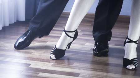 jive: Male and female ballroom, standard, sport dance, latin and salsa couple dancers feet and shoes in dance academy school rehearsal room dancing salsa.