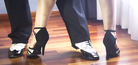 tangoing: Male and female ballroom, standard, sport dance, latin and salsa couple dancers feet and shoes in dance academy school rehearsal room dancing salsa.