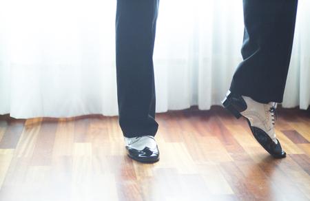 a rehearsal: Male ballroom, standard, sport dance, latin and salsa dancer feet and shoes in dance academy school rehearsal room dancing salsa.