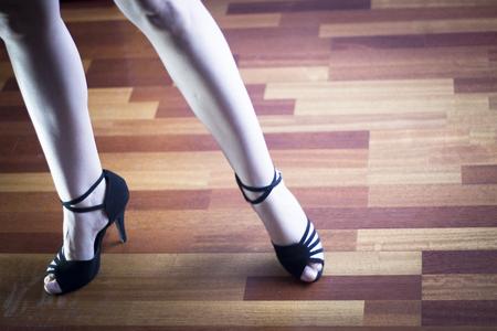 a rehearsal: Female ballroom, standard, sport dance, latin and salsa dancer feet and shoes in dance academy school rehearsal room dancing salsa.