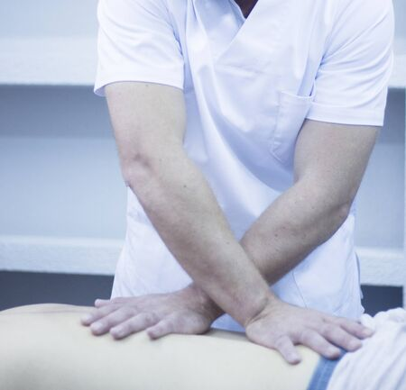 osteopath: Myofascial osteopathy physiotherapy treatment by physiotherapist and osteopath in physical therapy rehabilitation treatment on patient on back.