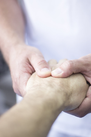 Myofascial osteopathy physiotherapy treatment by physiotherapist and osteopath in physical therapy rehabilitation treatment on patient on hand and wrist. Stock Photo