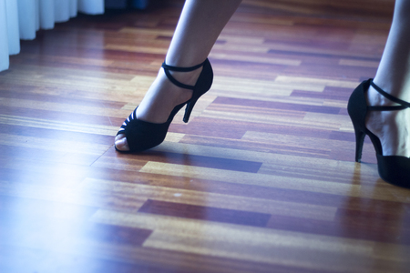 jive: Female ballroom, standard, sport dance, latin and salsa dancer feet and shoes in dance academy school rehearsal room dancing salsa.