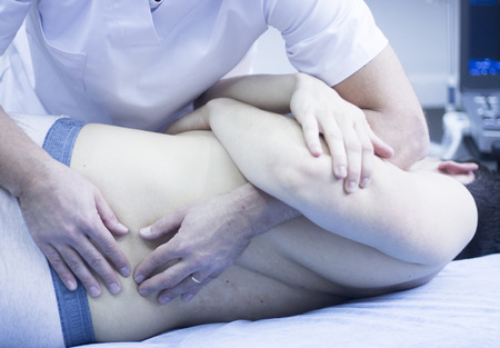 Myofascial osteopathy physiotherapy treatment by physiotherapist and osteopath in physical therapy rehabilitation treatment on patient on back.