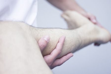 Myofascial osteopathy physiotherapy treatment by physiotherapist and osteopath in physical therapy rehabilitation treatment on patient on leg and knee joint. Stock Photo