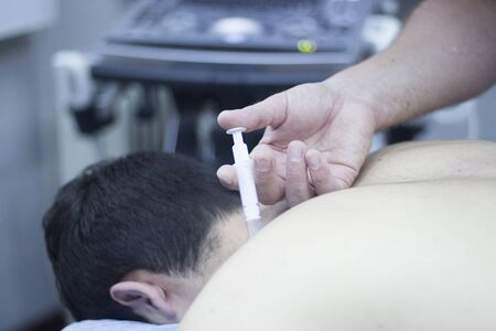 medical procedure: Intratissue Percutaneous Electrolysis EPI with needle injection medical procedure by physiotherapist doctor and patient in clinic.