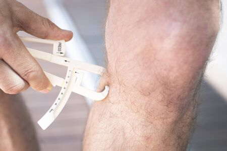 fits in: Slim attractive young man using fat caliper to measure bodyfat on leg.