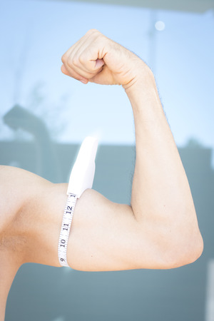 tricep: Slim attractive young man using measuring tape to measure weight loss o upper arm bicep and tricep.