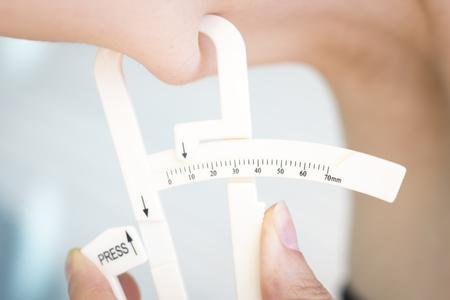 Slim attractive young lady wearing bikini in summer using fat caliper to measure bodyfat.
