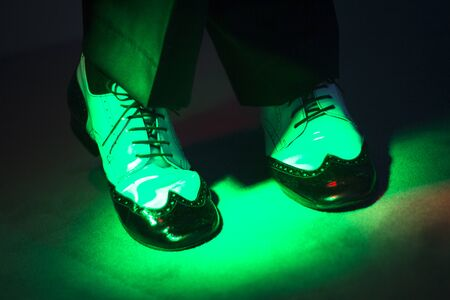 milonga: Male latin and salsa dancer in black and white jazz dancing shoes in light and dark on stage.