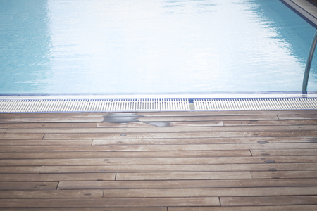 chillout: Hot summer by the outdoors swimming pool with wooden sundeck terrace. Stock Photo