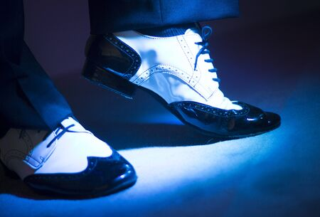 Male latin and salsa dancer in black and white jazz dancing shoes in light and dark blue lights on stage.