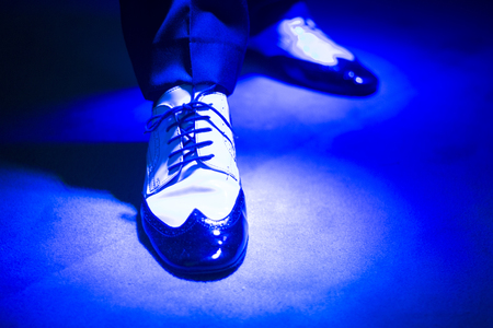 waltzing: Male latin and salsa dancer in black and white jazz dancing shoes in light and dark blue lights on stage.