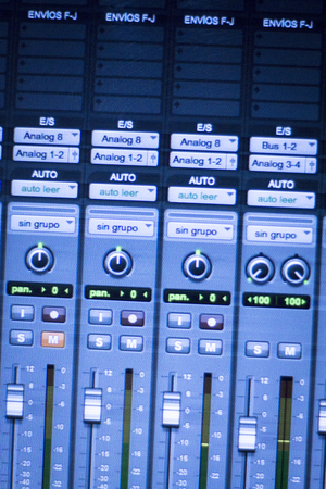equaliser: Professional sound recording audio studio digital equipment, amplifier, knobs and digital graphic equalizer controls on screen.