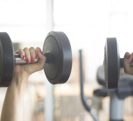 free weights: Female gym exercise dumbell free weights in fitness studio gymnasium for strength and resistance training and woman muscle bodybuilding.