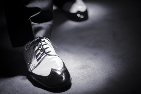 Male latin and salsa dancer in black and white jazz dancing shoes in light and dark on stage monochrome photo.