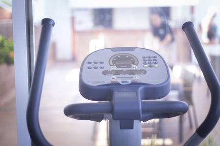 static bike: Gym bike exercise cycle machine for static indoor cycling in fitness and aerobic studio. Stock Photo