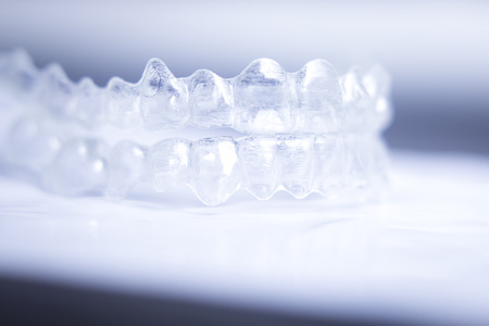 see through: Invisible teeth aligner cosmetic orthodontic brackets used to straighten and align teeth in patient with clear plastic see through aesthetic look.