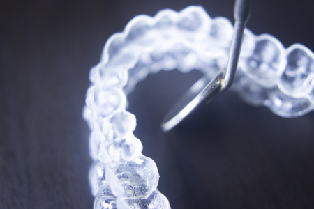 align: Invisible teeth aligner cosmetic orthodontic brackets used to straighten and align teeth in patient with clear plastic see through aesthetic look.