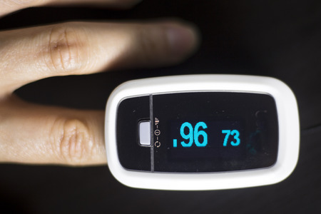 monitored: Portable hand held domestic cardiac finger pulse rate meter to show resting heart rate in monitored patient.