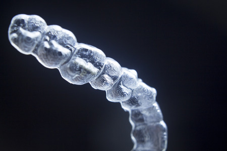 Invisible teeth aligner cosmetic orthodontic brackets used to straighten and align teeth in patient with clear plastic see through aesthetic look.