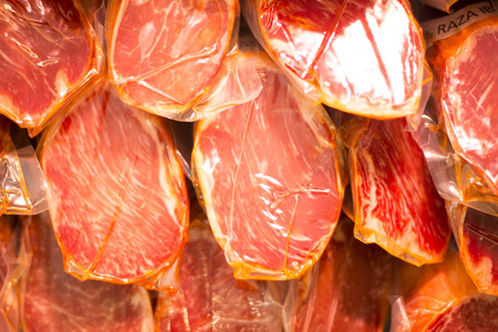 Spanish Iberian cured ham sausage cut for slices of cold meat in delicatessan.