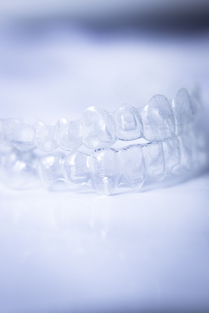 aligning: Invisible teeth aligner cosmetic orthodontic brackets used to straighten and align teeth in patient with clear plastic see through aesthetic look.