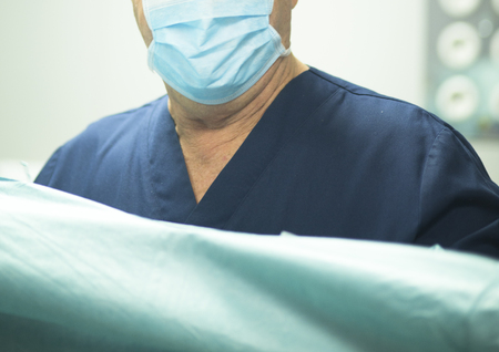 Surgeon in hospital surgery in sterile uniform scrubs in operating theater emergency room in surgical operation.