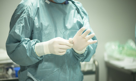 surgical operation: Surgeon in hospital surgery putting on gloves in sterile uniform scrubs in operating theater emergency room in surgical operation.