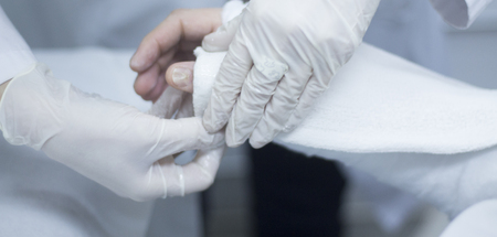 Doctor applying a plaster cast and bandages to patient forearm and wrist to immobilize after fracture injury. Stock Photo