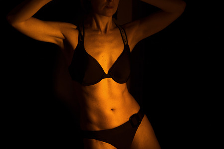 Sexy female nude slim athletic woman with naked torso, chest and abs. Toned athletic physique with natural fitness look.